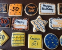 Sugar cookie rounds, stars, squares, diamonds and placards frosted in black & orange, and blue & gold