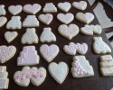 Sugar cookie hearts, wedding dresses and cakes frosted in ivory, white and pale pink