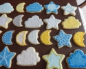 Sugar cookie stars, moons, and clouds frosted in blue, yellow, dark blue, white, silver, and gold