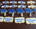 Sugar cookie graduation hats, diplomas, and placards frosted in blue and gold