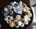 Cafe Macchiato Cups - Chocolate Dipped Citrus Strips - Chocolate Filled Hearts - Coconut Macaroons - Nut Balls - Raspberry Almond Thumbprints - Sugar cookie hearts and eighth notes frosted in navy and silver - Vanilla Crinkles (blue and silver sugar)