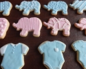Sugar cookie elephants and onesies frosted in pink and blue