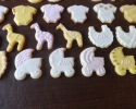 Sugar cookie rattles, onesies, bibs, strollers, rocking horses, elephants, and giraffes frosted in pink, white, and gold