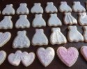 Sugar cookie wedding dresses and hearts frosted in light pink and white