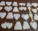 Sugar cookie wedding cakes, dresses, hearts, and champagne flutes frosted in blush and silver
