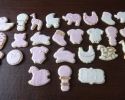 Sugar cookie baby shapes frosted in pink and white with gold accents