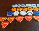 Sugar cookie Penn State logos, squares and rectangles frosted in light blue and black, Superman logos, and Dukes of Hazzard logo