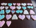 Sugar cookie hearts and wedding cakes frosted in pink and turquoise