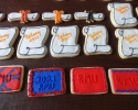 Sugar cookie graduation scrolls and rectangles frosted in red and royal blue, and black and orange