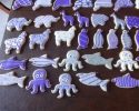 Sugar cookie sharks, llamas, octopi, penguins, elephants, and panthers frosted in purple and silver