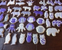 Sugar cookie owls, penguins, octopi, elephants, tigers and monkeys frosted in purple and silver
