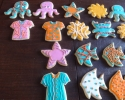 Sugar cookie octopi, crabs, suns, starfish, Hawaiian shirts, and angel fish frosted in pink, orange and turquoise