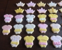 Sugar cookie onesies with tutus and crowns frosted in pink, white, and gold