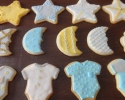 Sugar cookie stars, clouds, rattles, onesies, and moons frosted in ivory, gold, gray, and blue