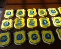 Sugar cookie badges frosted in yellow and blue