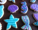 Sugar cookie sea shells, sea stars, sea horses, and mermaid tails frosted in purple and teal
