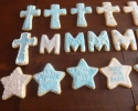 Sugar cookie crosses, Ms, and stars frosted in blue and white