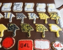Sugar cookie graduation scrolls, rectangles, stars, and placards frosted in black and yellow, and red and black