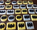Round and rectangular sugar cookies frosted in yellow and gray with Batman logo