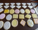 Sugar cookie ovals, squares, and diamonds frosted in blush, pink, white, and gold