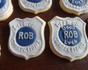 Sugar cookie stars, placards, rounds, and badges frosted in navy and silver