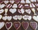 Sugar cookie wedding cakes, dresses, hearts, and champagne flutes frosted in burgundy and white