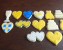 Sugar cookie champagne flutes, hearts, wedding dresses, and cakes frosted in yellow and royal blue
