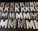 Sugar cookie Ms and Ks frosted in beige, black, cream, and white